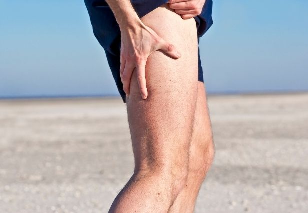 runner holding his leg due to muscle shrinking
