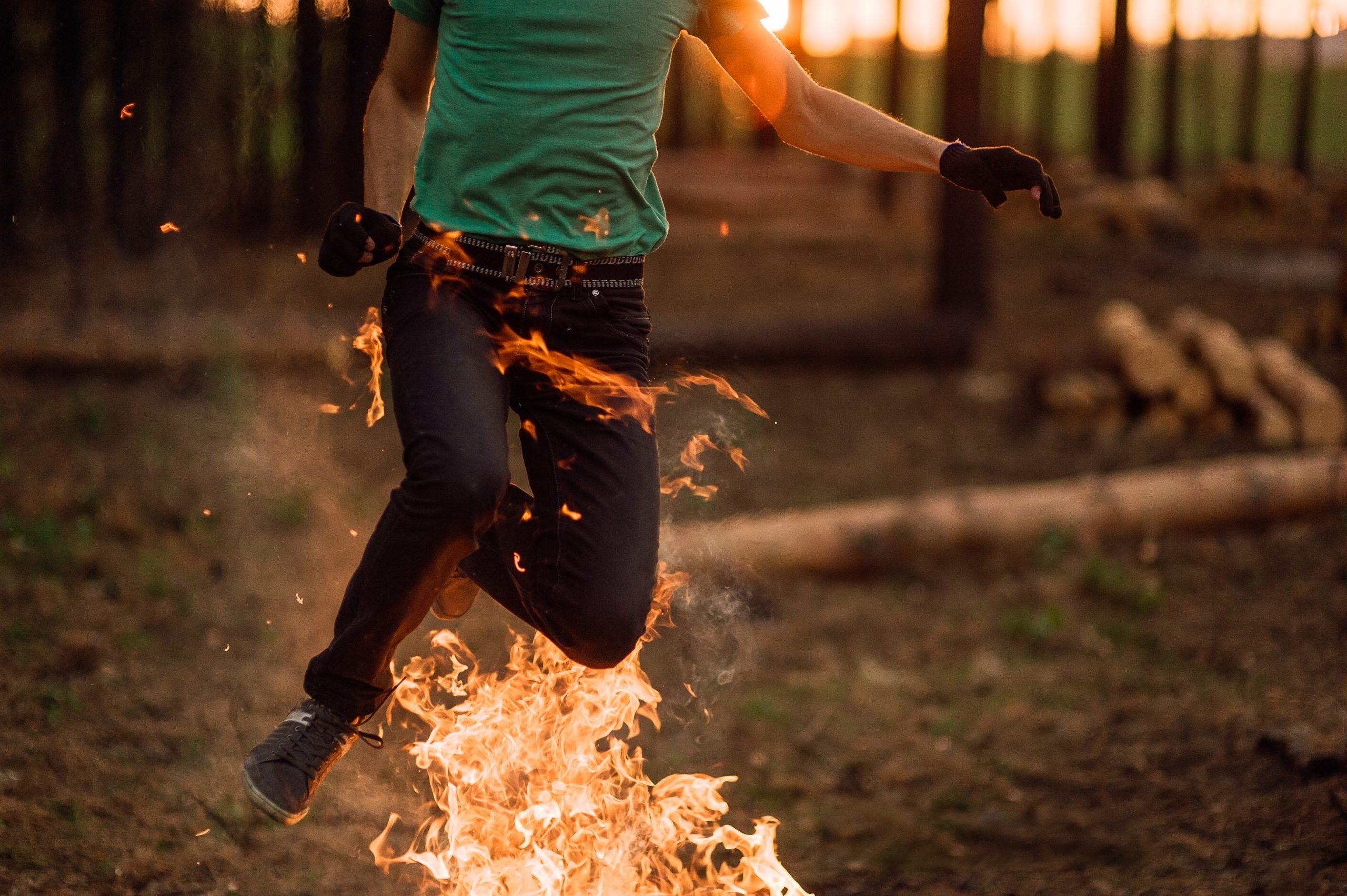 man is jumping over a fire